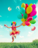 Child with toy balloons in spring field Stock Image