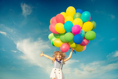Child with toy balloons in spring field stock images