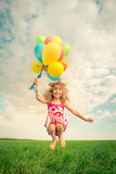 Child with toy balloons in spring field Royalty Free Stock Photography