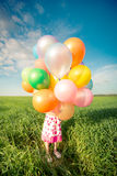 Child with toy balloons in spring field Royalty Free Stock Image