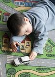 Child with toy car. Small child boy playing on a road themed carpet with a toy car Royalty Free Stock Photos