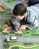 Child with toy car. Small child boy playing on a road themed carpet with a toy car; top view Stock Photography