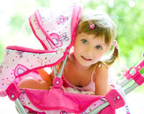 Child with toy carriage. Cute little girl with her toy carriage stock image