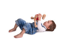 The child with a toy cries. The child with a toy lies on a floor and cries Royalty Free Stock Photos
