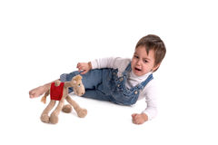 The child with a toy cries. The child with a toy lies on a floor and cries Royalty Free Stock Image