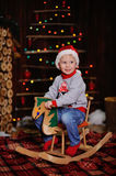 Child on a toy horse  the background of Christmas tree Royalty Free Stock Photos