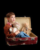 Child with toy in old suitcase. Isolated on black background Royalty Free Stock Photography