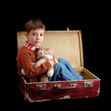 Child with toy in old suitcase. Isolated on black background Stock Photo
