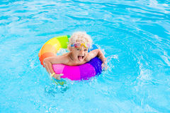 Child with toy ring in swimming pool. Happy little boy playing with colorful inflatable ring in outdoor swimming pool on hot summer day. Kids learn to swim Royalty Free Stock Photo