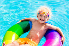 Child with toy ring in swimming pool. Happy little boy playing with colorful inflatable ring in outdoor swimming pool on hot summer day. Kids learn to swim Stock Photography
