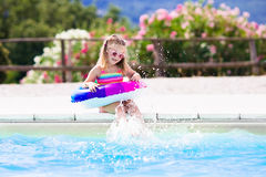Child with toy ring in swimming pool. Happy little girl playing with colorful inflatable ring in outdoor swimming pool on hot summer day. Kids learn to swim Royalty Free Stock Photos