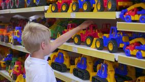 A child in a toy store looking at a car stock video