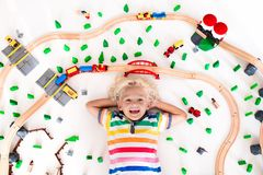 Child with toy train. Kids wooden railway. Kids play with toy train railway. Child playing with wooden trains. Toys for little boy. Preschooler building rail Stock Photos