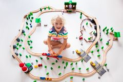 Child with toy train. Kids wooden railway. Stock Photo