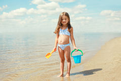 Child with toys and having fun on the beach near sea in summer. Sunny day Stock Photo
