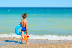Child with toys, looking at the sea Royalty Free Stock Photos