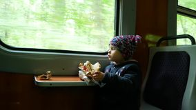 Child in the train near the window. The girl eats a pie, sitting in the train car. stock video footage