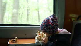 Child in the train near the window. The girl eats a pie, sitting in the train car. stock video