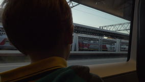 Child in train waving hand to grandparents as he leaving stock video footage