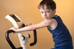 The child is trained on a stationary bike . Healthy lifestyle. Stock Images