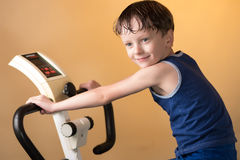 The child is trained on a stationary bike . Healthy lifestyle. Royalty Free Stock Photography