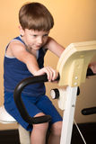 The child is trained on a stationary bike . Healthy lifestyle. Royalty Free Stock Image