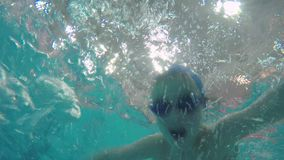 Child training in swimming pool. Boy having a training in the pool. Underwater shot of a swimming boy in goggles and cap stock video footage