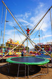 Child on trampolin. USTRONIE MORSKIE, POLAND - JULY 20, 2015: Tied child jumping on a trampolin at a fair Stock Photos