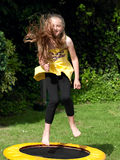 Child on trampoline. CLoseup of young girl bouncing on small trampoline on lawn Stock Photo
