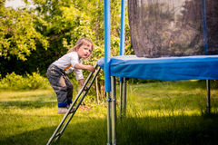 Child on trampoline ladder. Little child climping on big trampoline - outdoors in backyard Royalty Free Stock Images