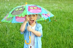 Child Trapped in Rain Storm with Umbrella Royalty Free Stock Photography