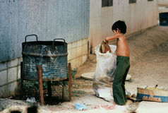 Child trash recycler III. Cambodian boy retrieving cardboard from trash can at a refugee camp in Panatnikhom, Chonburi, Thailand, 1984 Royalty Free Stock Photography