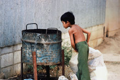 Child trash recycler. Cambodian boy searches through trash can Royalty Free Stock Photos