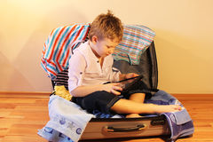 Child in the travel suitcase. Boy sits in a suitcase with clothes and beach towels Stock Photos