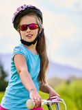 Child traveling bicycle in rainbow goggles and helmet in park. Royalty Free Stock Photo