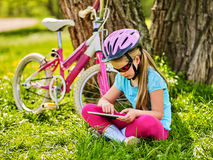 Child traveling bicycle in summer park. Girl watch tablet computer. Child traveling bicycle in summer park. Bicyclist little girl watch on tablet computer. Kid Royalty Free Stock Image