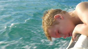 Child traveling by boat and trying to touch water. Boy leaning on the boat border and moving hand down to water to feel the splashes on high speed stock video footage