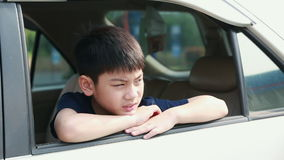 Child Traveling by Car, Asian boy Looking out of Window During stop, Trip in city.  stock video footage