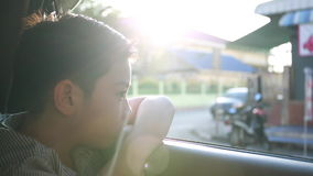Child Traveling by Car, Asian boy Looking out of Window During stop, Trip in city,with sun flare.  stock footage