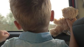 Child traveling in car with favourite teddy bear. Slow motion close-up shot of a a little boy traveling by car with favourite toy bear. He hugging soft friend stock footage