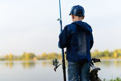 A fisherman boy on the river bank with a fishing rod in his hand. The child is traveling down the river on a bike with a fishing rod in summer.It stands on the Stock Image