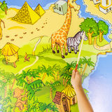 Child is traveling with a stick on the map of the world Royalty Free Stock Photos