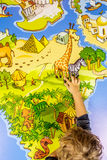 Child is traveling with a stick on the map of the world Royalty Free Stock Photo