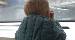 Child traveling in subway train. Back view of a boy looking out the window of subway train moving through the city into the tunnel stock video