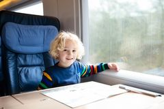 Kids travel by train. Railway trip with child. Child traveling by train. Little kid in a high speed express train on family vacation in Europe. Travel by stock images