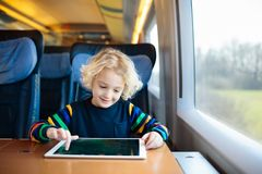 Kids travel by train. Railway trip with child. Child traveling by train. Little kid in a high speed express train on family vacation in Europe. Travel by stock photos
