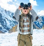 Child travellers looking into the distance through binoculars. Winter on higher level of fun. modern mother and child travellers in the front of mountain scenery stock photos