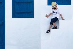 Cheerful Boy on the Background of the White-Blue Building. The Greek Concept stock photo