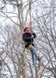 Child in tree harness hangs in the air. March 17, 2019  New Carlisle Indiana USA; a young child strapped into a tree harness, hangs in midair at an event in st stock image