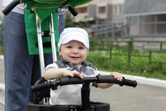 Child on tricycle with push handle Stock Photo